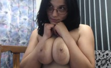 Busty brunette geek fondles her big tits and hairless pussy